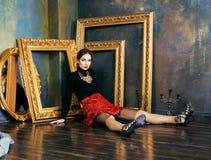 Tömmer den rika brunettkvinnan för skönhet i lyxigt inre near ramar, tappningelegans Royaltyfri Fotografi