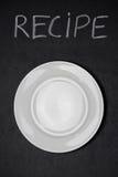 Tömmer skriftlig vit krita för recepttiteln och plattan på en svart tavla Royaltyfri Bild
