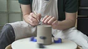 Töpfer schnitzt eine Kerbe auf der Unterseite der Tonwaren auf einem drehenden Kreis stock footage