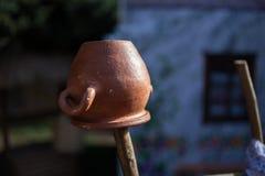 Töpferwarenkrug, der an einem Bretterzaun hängt Dorfart stockfotografie