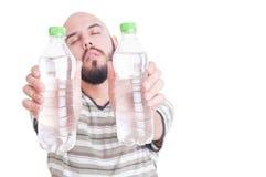 Törstig man som rymmer två flaskor av kallt vatten arkivfoto