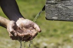 Törstiga händer som tar vatten från brunnen Arkivfoton