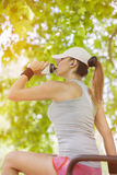 Törstigt dricksvatten för ung kvinna, medan sitta royaltyfria foton