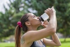 Törstigt dricksvatten för ung kvinna, medan vila royaltyfri foto