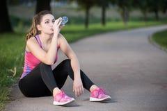 Törstigt kvinnadricksvatten som ska återfås krafter, når att ha joggat Royaltyfri Fotografi