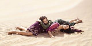 Törstigt lägga för kvinnor i en öken Borttappat i ökendurindsandshtorm arkivfoto