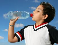 Törstigt pojkedricksvatten ut royaltyfri foto