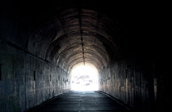 Túnel oscuro largo con la luz en el extremo Foto de archivo