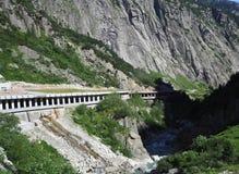Túnel pedregoso escénico del camino en las montañas suizas en SUIZA cerca de la ciudad de Andermatt con paisaje alpino de la gama Imagen de archivo