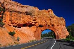 Túnel rojo del camino del arco en la barranca del bryce imagenes de archivo
