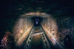 Túnel subterráneo abandonado del ladrillo de la alcantarilla, pasillo industrial sucio oscuro, opinión de perspectiva del tubo Foto de archivo libre de regalías
