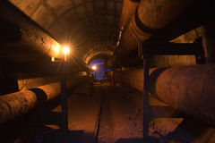 Túnel subterráneo redondo del conducto de la calefacción con los tubos oxidados fotos de archivo