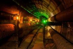 Túnel sucio del conducto de la calefacción con la tubería oxidada imagenes de archivo