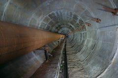 Túnel técnico subterráneo sucio redondo viejo del conducto de la calefacción con la tubería oxidada imagenes de archivo