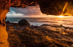 Túneles costeros de la roca a las repisas del acantilado con luz del sol de la madrugada fotografía de archivo