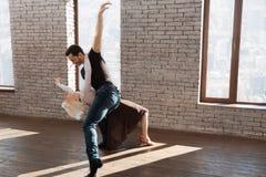 Tüchtiger Tanzlehrer, der mit älterer Frau am Ballsaal tangoing ist Lizenzfreie Stockbilder