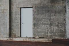 Tür auf dem Hintergrund einer konkreten Beschaffenheitswand Stockfotos