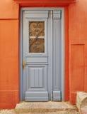 Tür auf orange Hausmauer Lizenzfreie Stockbilder