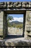 Tür in der Steinwand schaut heraus zu den Bergen und zum blauen Himmel mit w Lizenzfreies Stockfoto