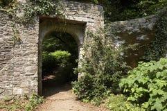 Tür durch zu einem üppigen grünen Garten Stockfotografie