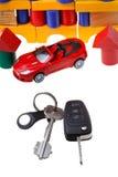Tür, Fahrzeugschlüssel, rotes Automodell und Blockhaus Lizenzfreies Stockfoto