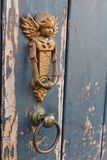 Tür-Klopfer in Form des Engels auf einer rustikalen Holztür Stockbilder