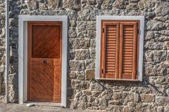 Tür und Fenster in einer rustikalen Wand Stockfoto