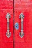 Türgriffe auf roter Holztür Lizenzfreie Stockfotografie