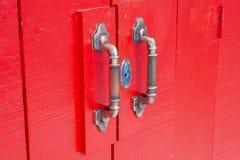 Türgriffe auf roter Holztür Stockfoto