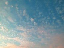Türkis-blauer Himmel mit den weißen und rosa Wolken Stockbilder
