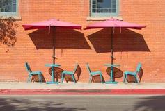 Türkis-Café-Tabellen und Stühle mit rosa Regenschirmen stockbild