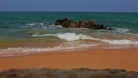 Türkis-Meereswoge-Brandungs-Abbruch auf Felsen durch Strand gegen Himmel stock footage