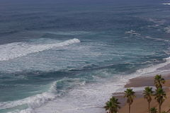 Türkisblaumeereswogen auf Sand setzen mit Palmen auf den Strand Stockfotos