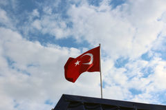 Türkische Flagge vor dem hintergrund des Sommerhimmels Lizenzfreies Stockfoto