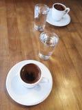 Türkische Kaffeetassen und Wasser auf Holztisch Stockfotografie
