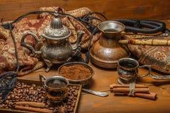 Türkischer Kaffee in den silbernen Tellern mit gemahlenem Kaffee und Kaffeebohnen, Zimt, Anis stockfoto