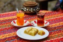 Türkischer orange und schwarzer Tee in den traditionellen Gläsern und im Baklava Lizenzfreie Stockfotos