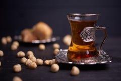 Türkischer Tee in den traditionellen Gläsern mit Nüssen und Baklava auf hölzernem Hintergrund lizenzfreies stockbild