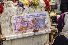 Türkischer Teppichweber spinnt auf einem Webstuhl auf den Straßen Lizenzfreie Stockfotografie