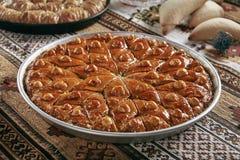 Türkisches Baklava in einem runden Metallbehälter auf Weinlese-traditioneller Tischdecke lizenzfreies stockbild