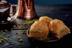 Türkisches Baklava nahe Walnüssen auf schwarzem hölzernem Hintergrund lizenzfreies stockbild