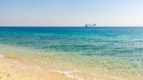Türkismeer mit hellen Kräuselungen auf dem Wasser und einem großen Kreuzfahrtschiff auf dem Horizont lizenzfreie stockbilder