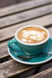 Türkisschale mit Kaffee, gemalter Bär, steht auf einem Holztisch Stockfotografie