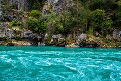 Türkiswasser von einem Fluss mit Felsen, Klippen und Bäumen im Hintergrund in Norwegen Lizenzfreie Stockbilder