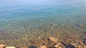 Türkiswasserfarbe auf dem Strand mit einem großen Meerblick lizenzfreies stockbild