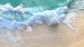 Türkiswellen, die auf einem sandigen Strand zusammenstoßen stock video