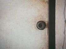 Türknauf auf alter Holztür und gebrochener Wand Stockbild