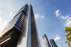 Türme von Geschäftswolkenkratzern auf dem blauen Himmel mit Weiß bewölkt Hintergrund lizenzfreie stockfotografie