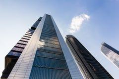 Türme von Geschäftswolkenkratzern auf dem blauen Himmel mit Weiß bewölkt Hintergrund lizenzfreie stockbilder