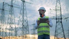 Türme von Stromleitungen und ein männlicher Techniker, der eine Tablette betreibt stock video